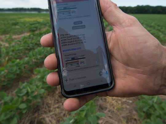 Jay Baxter, farm manager at Baxter Farms in Georgetown, uses his phone to check soybean prices.