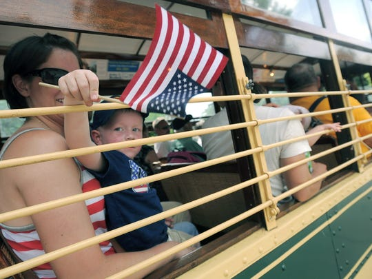 Maddox Sorenson, 3 of Loveland, waves a flag as he waits to ride the Fort Collins City Railway's trolley during the Fourth of July 2013 celebration at City Park.sorenson is held by his mother Jhoni.