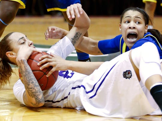 James Madison's Jazmon Gwathmey (left) and Delaware's Erika Brown scramble for a loose ball in the first half of a CAA tournament semifinal at the Show Place Arena in Upper Marlboro, Md. Friday.