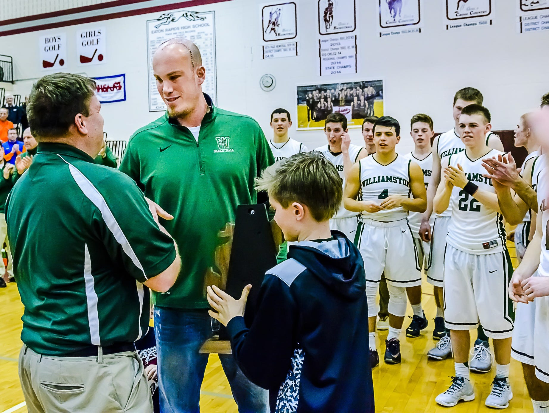 Williamston boys basketball coach Jason Bauer, second from left, accepts the Class B regional trophy after the Hornets win over Stockbridge in March at Eaton Rapids High School. Bauer has been sidelined because of brain tumors that were removed last spring.