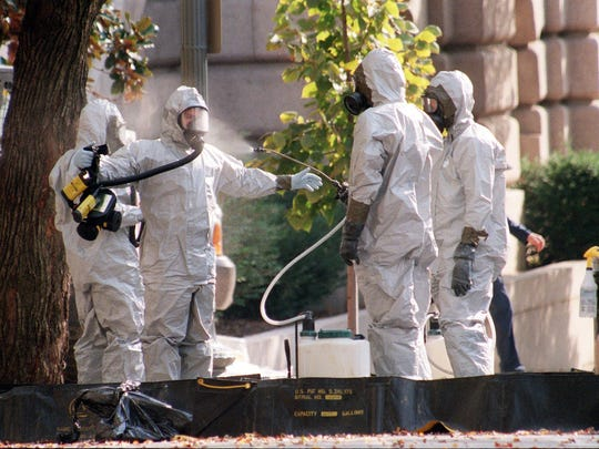 A hazardous materials unit worker is hosed down on Capitol Hill in Washington, D.C., on Oct. 23, 2001, where workers continued inspecting buildings and offices for anthrax contamination.
