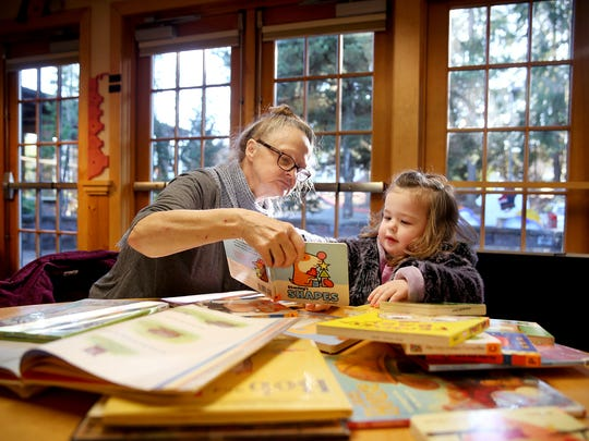 File photo — Loretta Boykin, left, from Suquamish, and her great-granddaughter Riley Coulter, 2, look at books in the children's section of the Poulsbo Library.