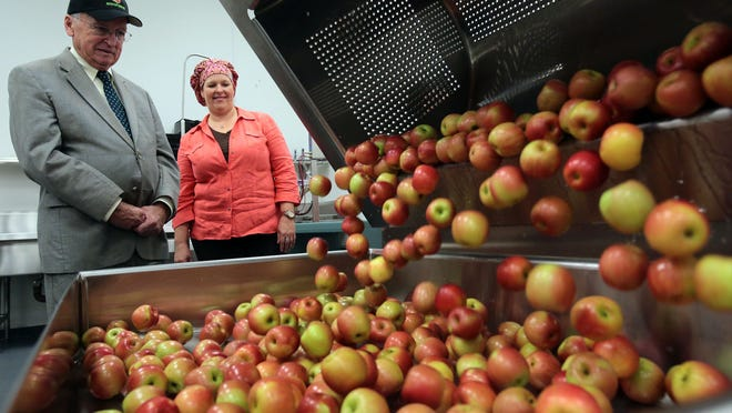 Apples fall out of a produce washer as Palm Springs Unified School District's Nutrition Services Director Stephanie Bruce and Kevin Concannon, U.S. Department of Agriculture under secretary for food, nutrition, and consumer services, look on Tuesday.