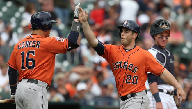 Astros' Preston Tucker, right, high fives Hank Conger after hitting a home run to tie the Tigers in the ninth inning on Thursday.