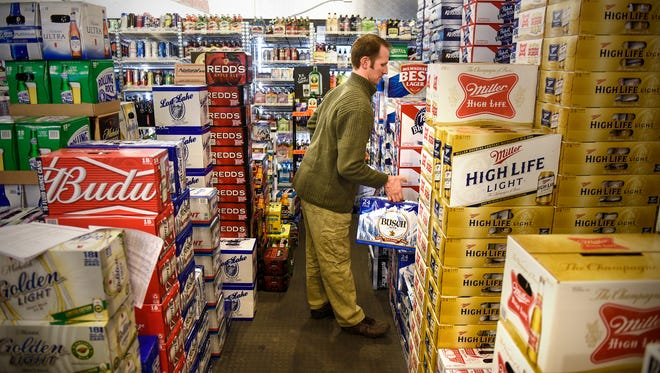 David Vos moves cases of beer in the large walk-in cooler Monday, Feb. 27, at The Liquor Shoppe on 25th in St. Cloud.