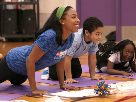 Kerrie Trahan, a Work It Out Program and Volunteer Coordinator, leads the third graders at the Charles Wright Academy of Arts and Sciences in Detroit, in a yoga pose during Yoga class at the school's gym Tuesday, November 17. Third graders Jashawn Johnson, 8, and Breah Carter, 8, follow Trahan's lead.