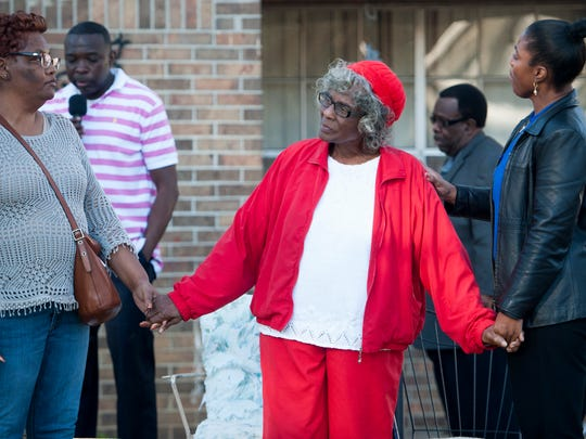 Nellie Ruth Gunn, mother of Greg Gunn, holds hands as members of the community hold a vigil, on Saturday February 25, 2017, for Greg Gunn one year after he was shot and killed, by Montgomery police officer Aaron Cody Smith, in front of his home on McElvy Street in Montgomery, Ala.
