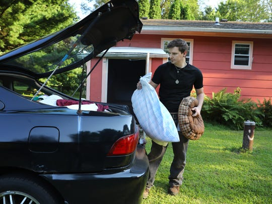 Cody McCormick, 29, packs belongings into his fiancé Breanna Kerssen's car in rural Monroe County on Aug. 1, 2017, as they prepare to move from his grandmother's house to an apartment in Sparta. McCormick faces ongoing difficulties with the GPS monitoring device he wears because of a conviction for a sex offense. Due to poor cell phone service at his grandmother's house, the GPS device would lose contact with the Madison-based monitoring center, resulting in false alerts.
