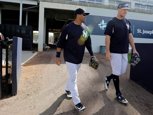 Seattle Seahawks quarterback Russell Wilson, left, walks onto the field with Aaron Judge before a baseball spring exhibition game against the Philadelphia Phillies, Monday, Feb. 26, 2018, in Tampa, Fla. (AP Photo/Lynne Sladky)