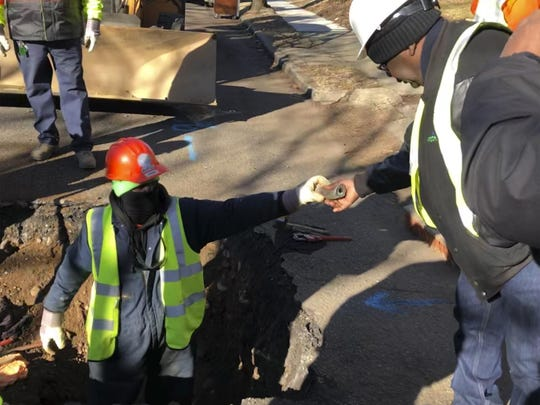 A worker hands a piece of lead pipe to a colleague as they work to remove water service lines Thursday in Trenton, N.J. The city announced it is replacing 37,000 lead pipes over five years as part of an an effort to remove the potentially harmful pipes.