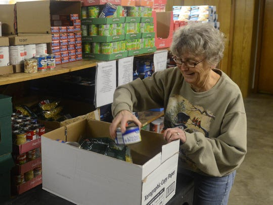Shirley Faist packs a box of food for a family while