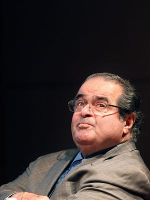 In this Oct. 18, 2011, file photo, U.S. Supreme Court justice Antonin Scalia looks into the balcony before addressing the Chicago-Kent College Law justice in Chicago. On Saturday, Feb. 13, 2016, the U.S. Marshals Service confirmed that Scalia died at the age of 79.