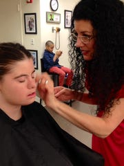 A makeup artist applies cosmetics to Jillian Daugherty prior to taping a segment for the Dr. Oz Show.