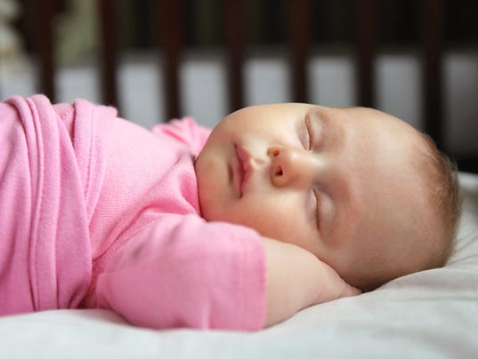 Sweet Newborn Baby Girl Asleep in Crib
