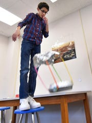 Michael Clark carefully watches the flight of his handmade aircraft from different heights inside the STEAM Lab at the Boys & Girls Club of Door County in Sturgeon Bay. The club received a grant from NASA to engineer Crew Exploration Vehicles (CEV) using simple components.