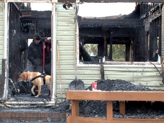 In this Asbury Park Press file photo, Ocean County Deputy Fire Marshal John P. Pasola leads his K-9 Sammy through the wreckage of a home on Division Avenue in Surf City on Monday, Jan. 9, 2017.