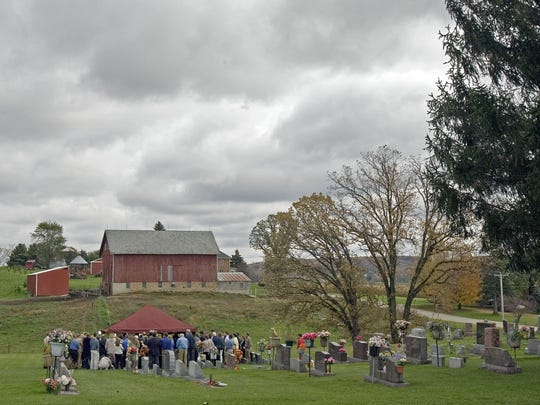 Friends and family gather at the burial of Weston Schools Principal John Klang Oct. 4, 2006, in Germantown, Wis. Klang was killed when a student shot him at the school.