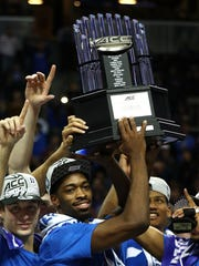 Duke players hold up the ACC tourney title trophy.
