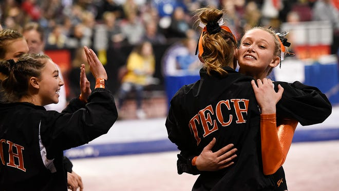 Tech's Taylor Brinkman gets a hug after  competing on the balance beam during the team Class AA championships Friday, Feb. 23, at the Maturi Pavilion in Minneapolis.