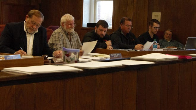 Marion County elected officials (from left) County Judge Terry Ott and justices of the peace Raymond Mayo, Carl McBee Jr., Gregg Alexander, Nicholas Nugent and Mike Scrima listen Tuesday night as an ordinance is read aloud during the Quorum Court meeting.