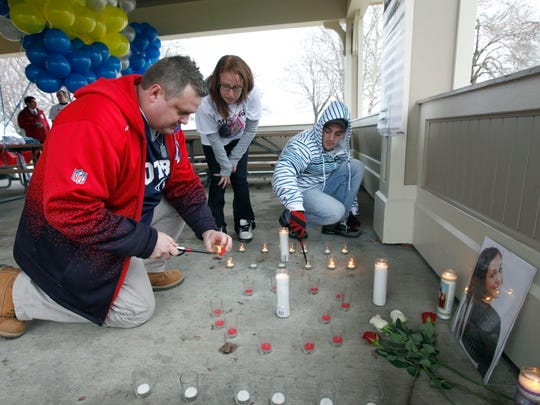 Chad Drexel, left, lights candles with help from family friends Bre Greeley and Matt Lessord of Spencerport at a vigil for his daughter Brittanee Drexel at Ontario Beach Park on April 26, 2014