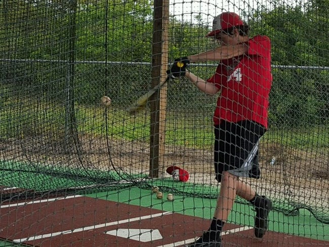 LaBelle Tyler Burton prepares for a game by hitting in the batting cage.