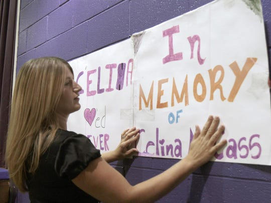 Matina Fenoff hangs a poster before a memorial service
