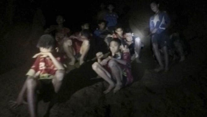A photo released by the Royal Thai Army on July 3, 2018 shows the missing 13 young members of a youth soccer team including their coach, moments after they were found inside the cave complex at Tham Luang cave in Khun Nam Nang Non Forest Park, Chiang Rai province, Thailand.