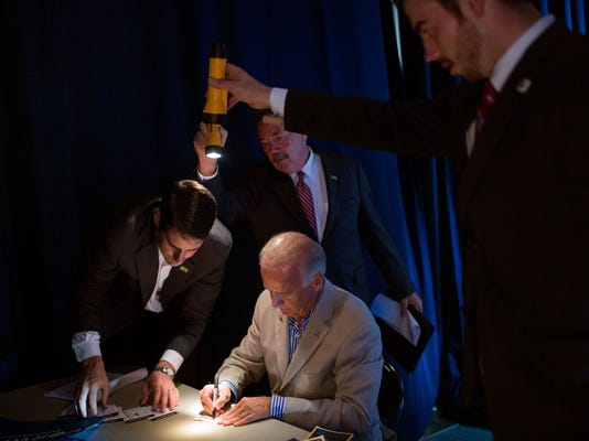 """""""David Lienemann made this unusual photo as staff held flashlights so the Vice President could see as he signed autographs backstage at West York Area High School in York, Pa."""" (Official White House Photo by David Lienemann)"""