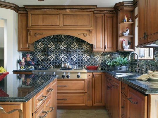 In this traditional kitchen renovation, the blue stained glass backsplash is accentuated by a beautiful repeating ivory pattern. Glazed maple cabinets provide warm contrast.