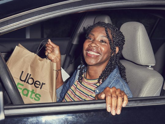 A woman in a car holding an Uber Eats bag.
