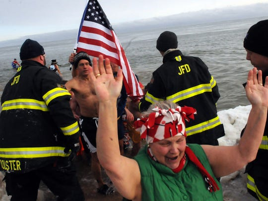 Jacksonport Fire Department members help Jacksonport Polar Bear Club members out of the frigid waters of Lake Michigan at last year's New Year's Day swim at Lakeside Park.