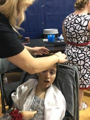 """A volunteer fixes Jessica's hair as part of the prom experience during a """"Night to Shine"""" sponsored by the Tim Tebow Foundation at the First Baptist Church of Merritt Island."""