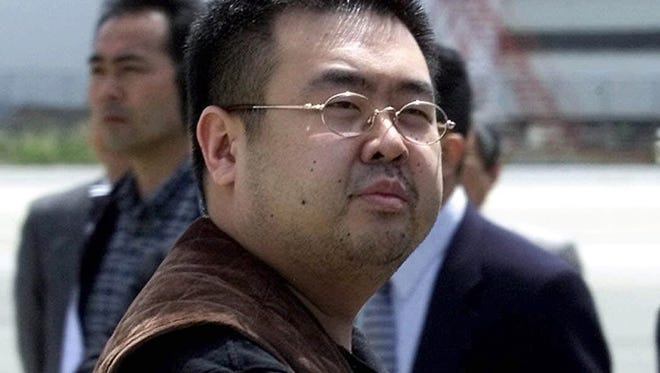 """In this May 4, 2001, file photo, a man believed to be Kim Jong Nam, the eldest son of then North Korean leader Kim Jong Il, looks at a battery of photographers as he exits a police van to board a plane to Beijing at Narita international airport in Narita, northeast of Tokyo. Police in Malaysia say the half brother of North Korea's leader who was killed in a Kuala Lumpur airport more than a week ago had a nerve agent on his eye and his face. A statement Friday, Feb. 24, 2017 from the inspector general of police said that a preliminary analysis from the Chemistry Department of Malaysia identified the agent at """"VX NERVE AGENT."""" (AP Photo/Shizuo Kambayashi, File)"""