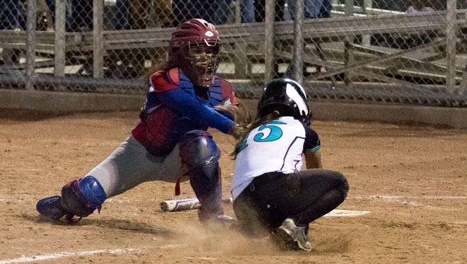 Las Cruces High catcher Brandy Lozoya tags Oñate's Marina Salcedo out at home plate in prep softball action at Field of Dreams Softball Complex Tuesday night.