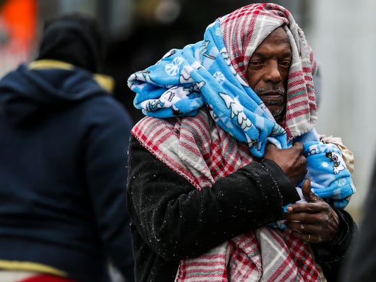 Michael Labingo wraps himself in blankets as the Star of Hope's Love in Action van delivers blankets and supplies to the homeless as temperatures hover in the 30s Tuesday, Jan. 2, 2018 in Houston.