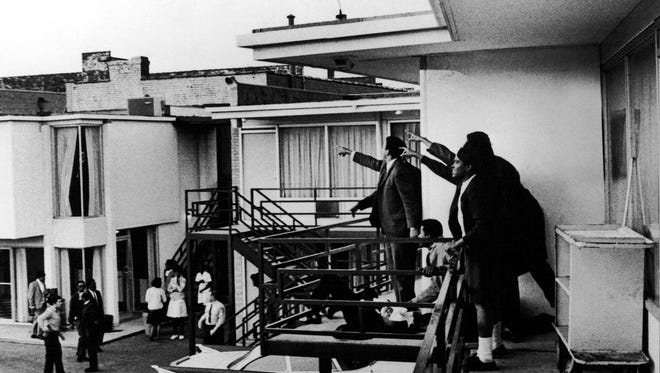 People on the balcony of Lorraine Motel point in direction of gun shots after assassination of civil rights leader Dr. Martin Luther King, Jr., who is lying at their feet.