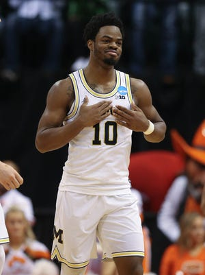 Michigan Wolverines guard Derrick Walton Jr. celebrates after scoring against Oklahoma State during the second half of U-M's 92-91 win Friday, March 17, 2017 at Bankers Life Fieldhouse in Indianapolis in the NCAA tournament.