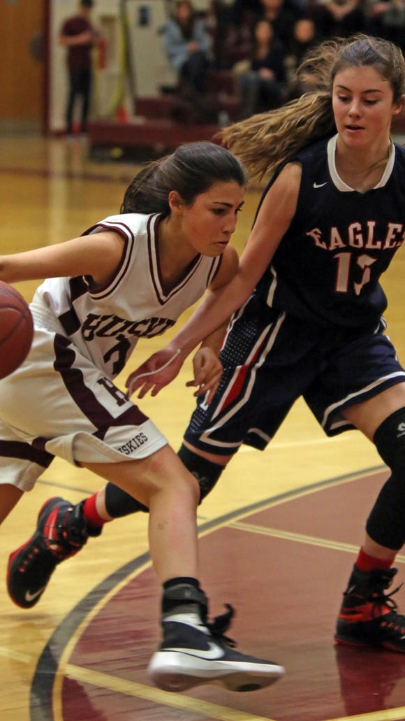 Harrison's Avery LaBarbera (3) dribbles pass Eastchester's Cassidy Mitchell (13) during game action at Harrison High School on Jan. 20, 2016.