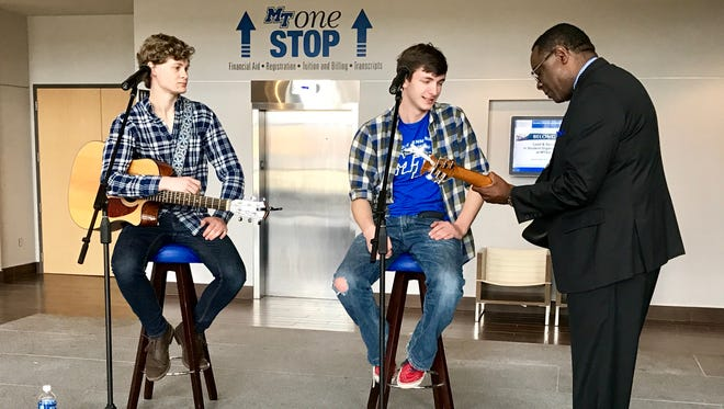 MTSU President Sidney A. McPhee (right) borrows a guitar from student songwriter Kenny Arnold (center) before Arnold and fellow student songwriter Cooper Gilliam performed at the start of a campus tour.