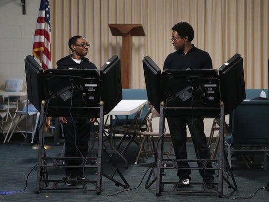 Wesley Bell Jr., 18, left, casts his vote alongside