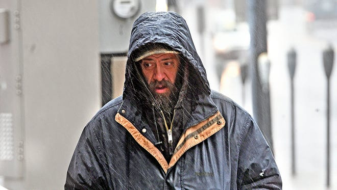 Thomas Lamson of Mansfield stays bundled up during a walk downtown Friday afternoon as the rain turned to ice.