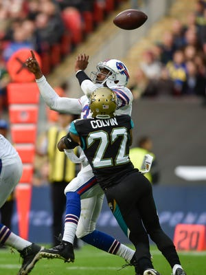 Jacksonville Jaguars cornerback Aaron Colvin (22) hits Buffalo Bills quarterback EJ Manuel (3) to force a fumble during the first half of the game at Wembley Stadium. Mandatory Credit: Steve Flynn-USA TODAY Sports