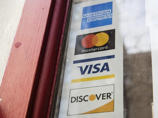 FILE - This Nov. 29, 2018, file photo shows are credit card logos posted on a store's door in Philadelphia. Simplify your taxes and maximize your income with a separate credit card for your side hustle. In addition to keeping all your business expenses in one place, it could help you with credit to build your business and rewards to extend your budget. (AP Photo/Matt Rourke, File)