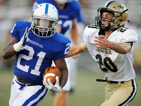 Memorial's Kenyon Ervin (21) runs past Jasper's Landon Betz (20) during Friday's game at Enlow Field at Bosse High School in Evansville.