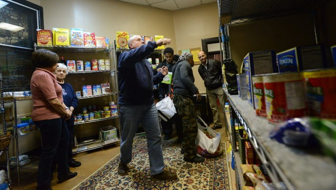 The Rev. Jim Petroccione, center, pointing out suggestions as Norwood Food Pantry gets busy, at The Church of the Holy Communion,