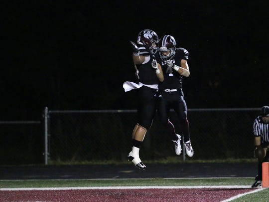 Joe Sparacio, left, and Keean Burlison celebrate the Lions' fifth touchdown in the first half of Friday night's first round of 2A playoffs between First Baptist and Village Academy in Naples.