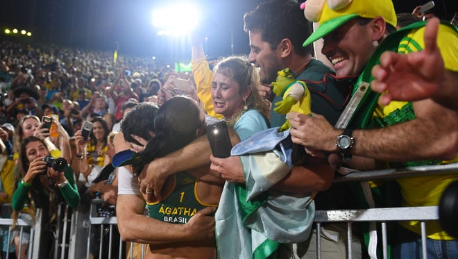 Brazil's Agatha celebrates with fans after she and Barbara won a semifinal match.