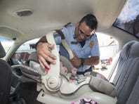 Nogales Fire Department Lt. Eduardo Canzales checks a car seat that proved to be properly installed for 6-month-old Anngel Lopez Salcido.