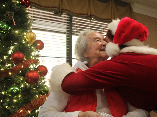 Anna Howell, 100 years old, gets a hug from Sandy Hill, who portrays Sandy Claus at Anderson area nursing homes.